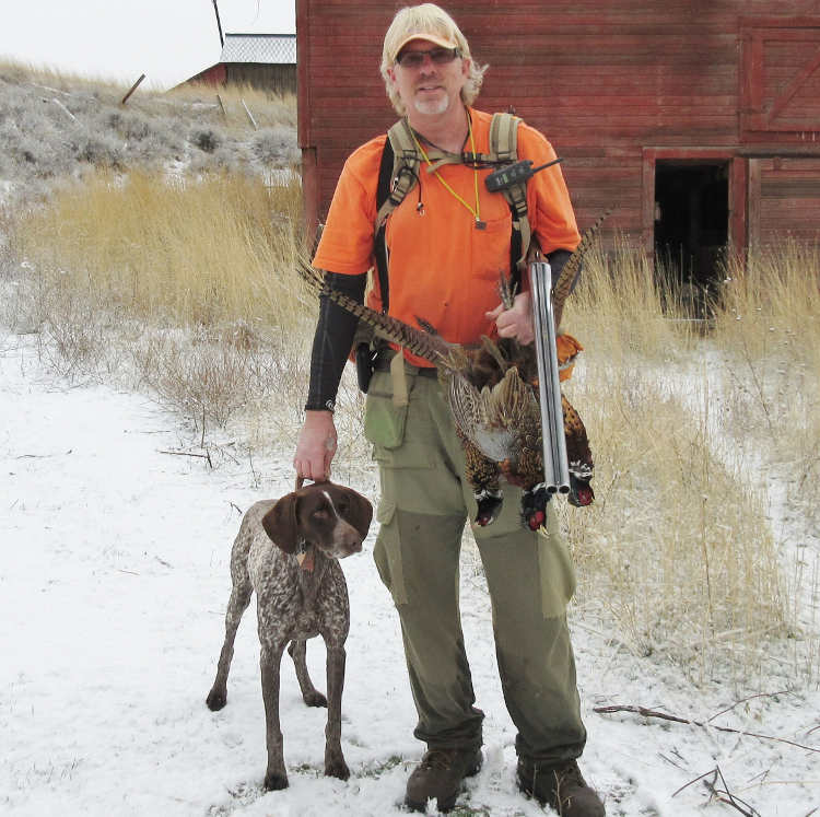 Man posing with dog and pheasant