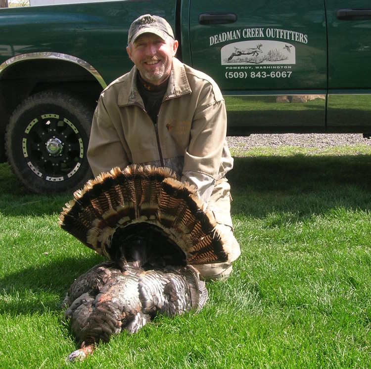 Man displaying his turkey at Deadman Creek Outfitters